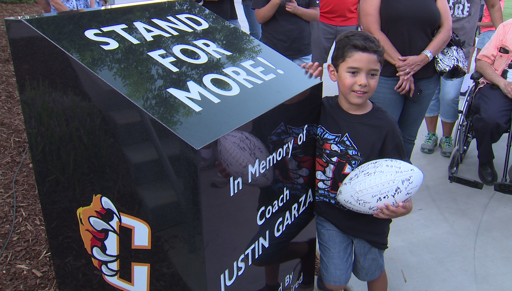 Joaquin Garza, Justin's son, standing next to his fathers new memorial.