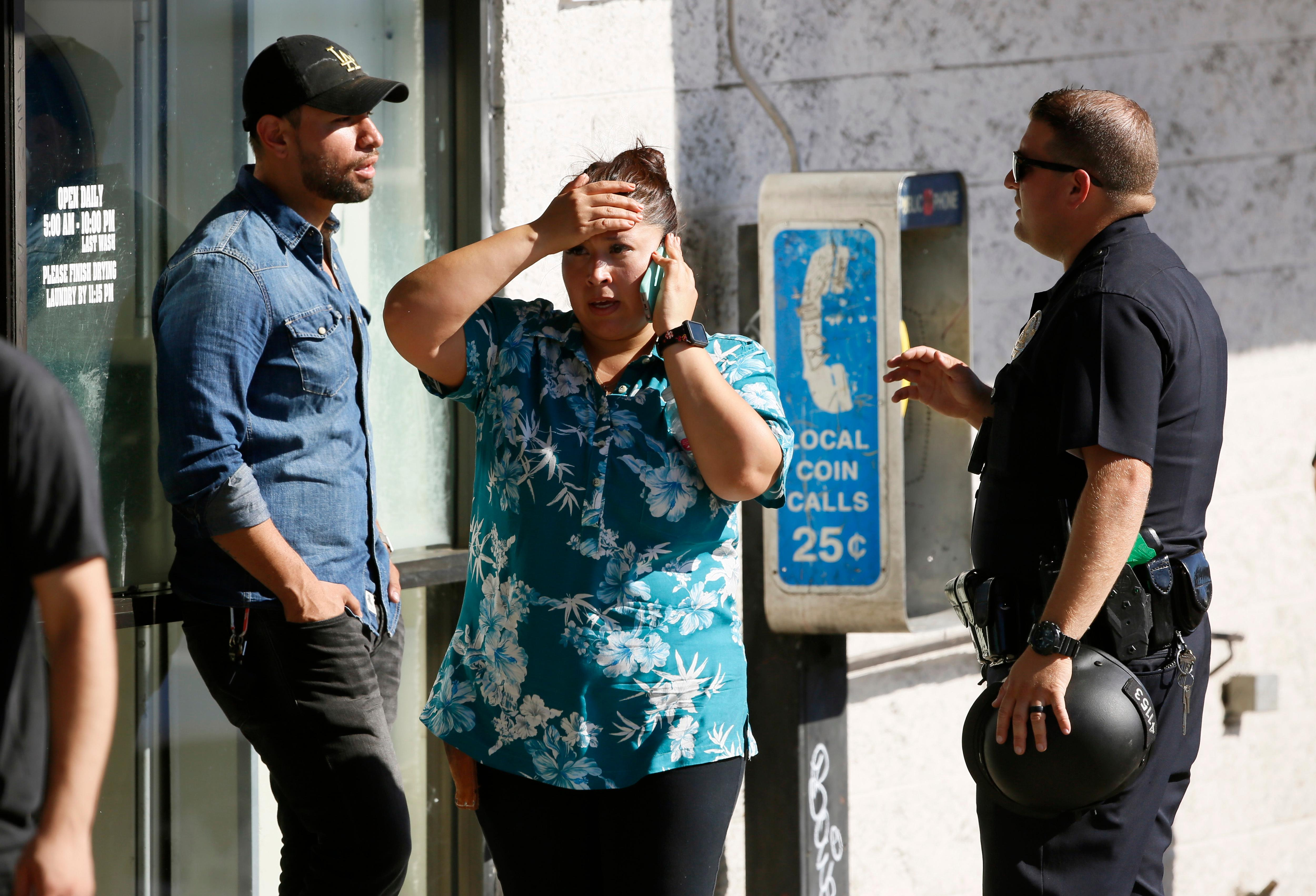 An unidentified Trader Joe's supermarket employee, center, talks on her phone as Los Angeles Police evacuate a group of witnesses after a gunman barricaded himself inside the store in Los Angeles Saturday, July 21, 2018. Police believe a man involved in a standoff at the Los Angeles supermarket shot his grandmother and girlfriend and then fired at officers during a pursuit before he crashed into a utility pole outside the supermarket and ran inside the store. About three hours after he took hostages in the store, the suspect surrendered. (AP Photo/Damian Dovarganes)