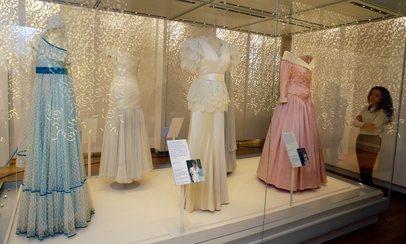 "A member of staff at Kensington Palace looks at a selection of dresses including at centre a dress by Bruce Oldfield of satin and lace over bodice and worn by Diana, Princess of Wales in 1990 at the Courtauld Institute of Art and a State Banquet at Buckingham Palace in 1991, on display during a media preview of an exhibition of 25 dresses and outfits worn by Diana entitled ""Diana: Her Fashion Story"" at Kensington Palace in London, Wednesday, Feb. 22, 2017. (AP Photo/Alastair Grant)"