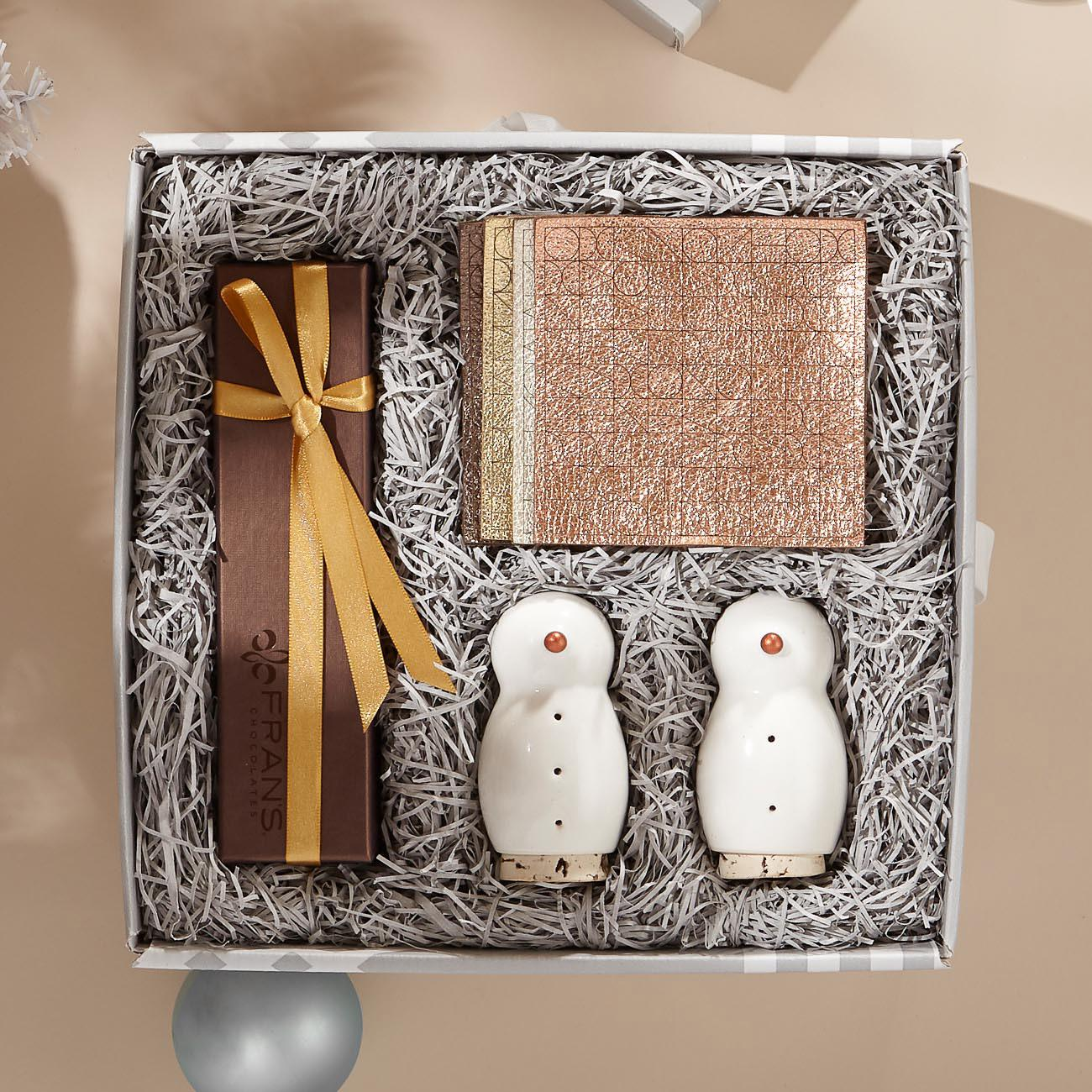 Seattle's Knack has amazing hostess sets, ready to go! A guaranteed favorite is their Winter's Glow Gift Set which contains 4 metallic leather coasters paired with a set of ceramic snowman salt and pepper shakers and a box of Fran's Chocolate's signature salted caramels. This sure-fire hostess gift  is one that will get you invited over again and again. (Image: Knack)<p></p>