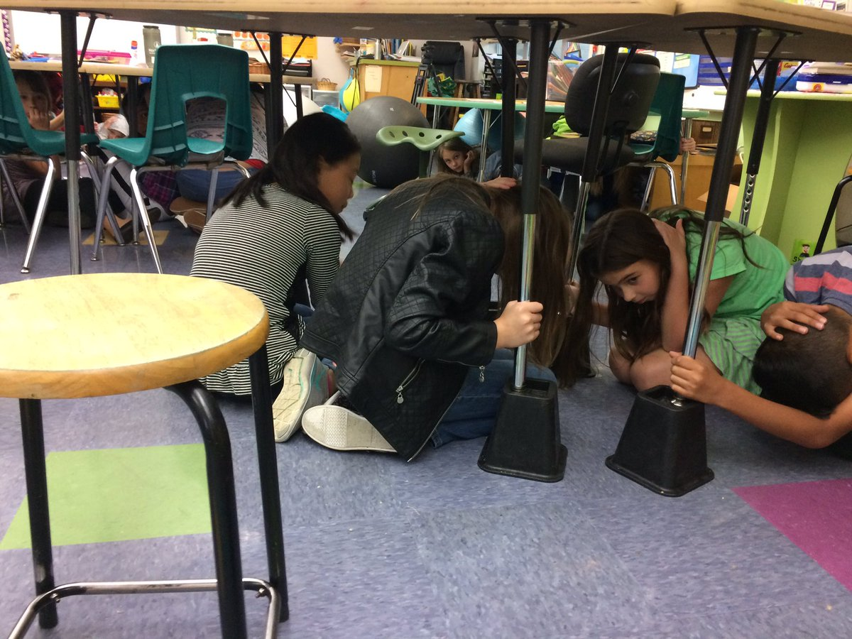 At McCornack Elementary school in Eugene on Wednesday, kids listened to instructions as they dropped, covered and held on under tables. (SBG)