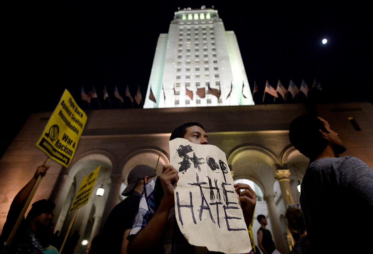 "Matt Castillo of Los Angeles holds a sign that reads ""Stop the Hate"" during a protest against President-elect, Donald Trump, in front of City Hall, Wednesday, Nov. 9, 2016 in Los Angeles. (Keith Birmingham/The Pasadena Star-News/SCNG via AP)"