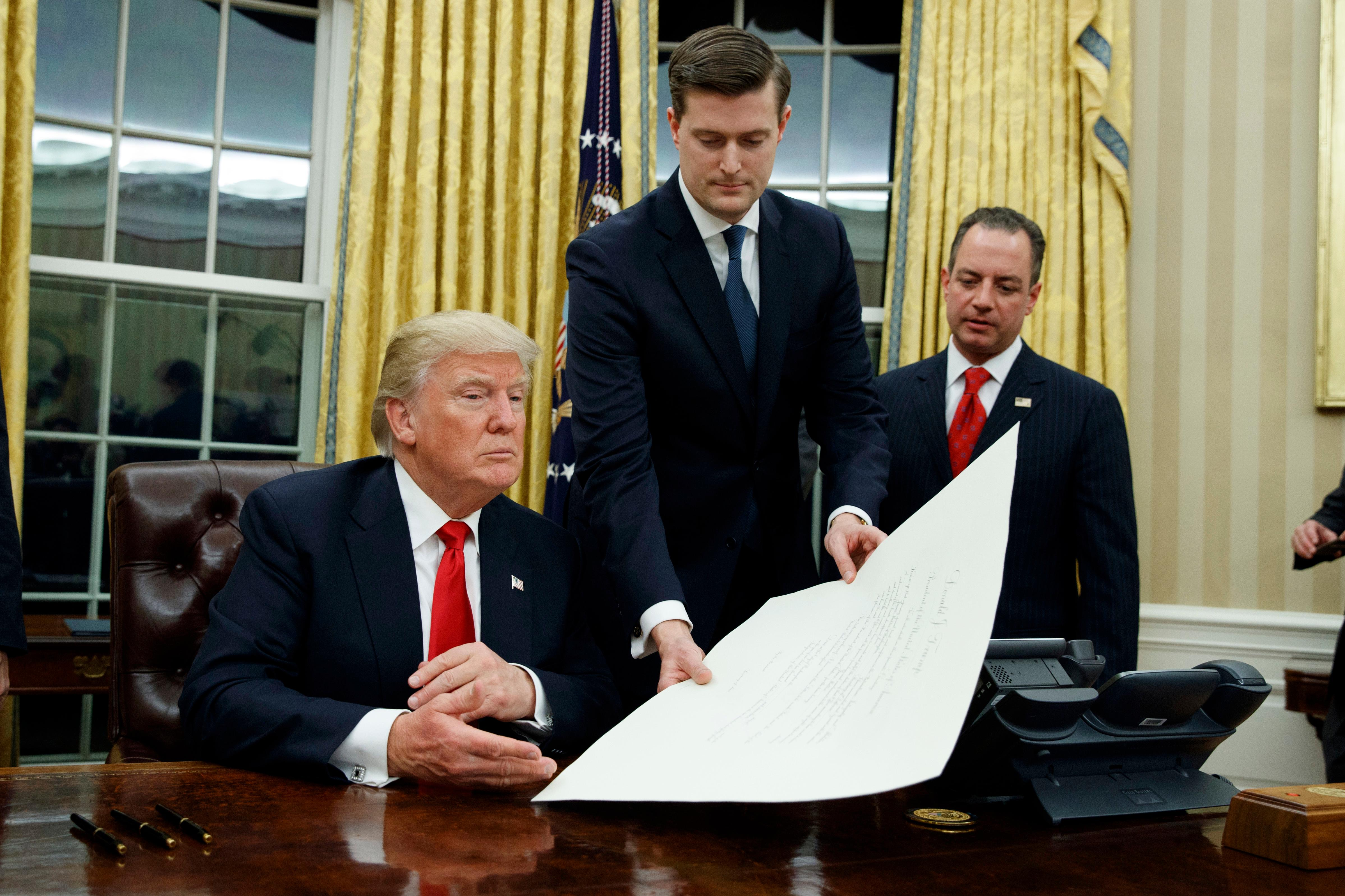 FILE - In this Jan. 20, 2017 file photo, White House Staff Secretary Rob Porter, center, hands President Donald Trump a confirmation order for James Mattis as defense secretary, in the Oval Office of the White House in Washington, as White House Chief of Staff Reince Priebus, right, watches.  Porter is stepping down following allegations of domestic abuse by his two ex-wives.   (AP Photo/Evan Vucci)