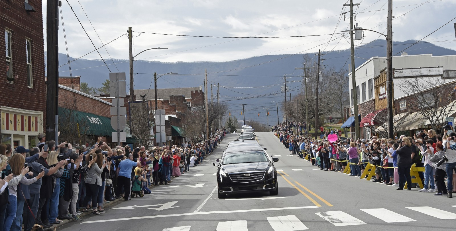People line the street to pay respects as the hearse carrying the body of Rev. Billy Graham travels through Black Mountain, N.C., Saturday, Feb. 24, 2018. (Kathy Kmonicek/pool photo)
