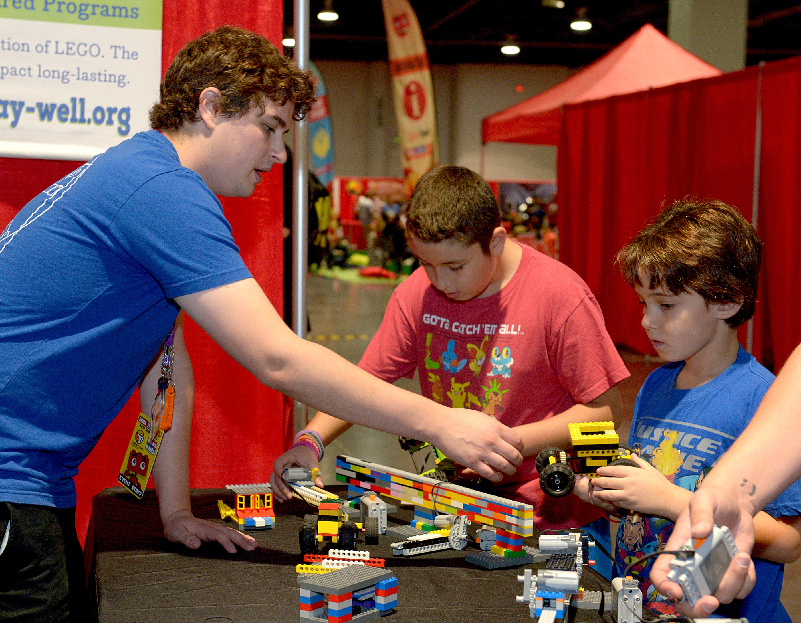 One of the Lego pros shows a young fan how he can attach a motor to his Lego car during the Brick Fest Live Lego Fan Experience at the Las Vegas Convention Center, September 9, 2017. [Glenn Pinkerton/Las Vegas News Bureau]