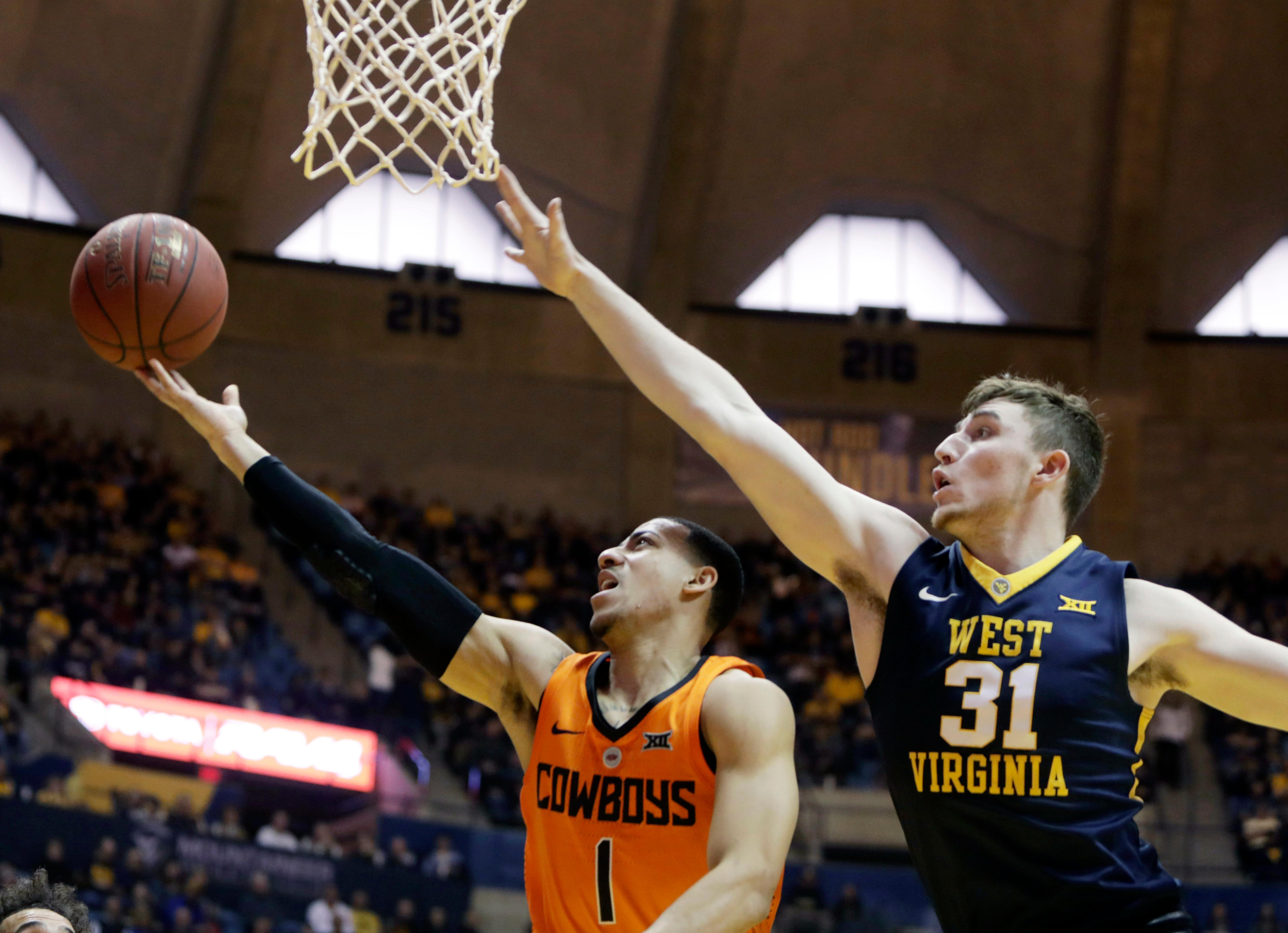 Oklahoma State guard Kendall Smith (1) drives as West Virginia forward Logan Routt (31) attempts to block his shot during the first half of an NCAA college basketball game Saturday, Feb. 10, 2018, in Morgantown, W.Va. (AP Photo/Raymond Thompson)