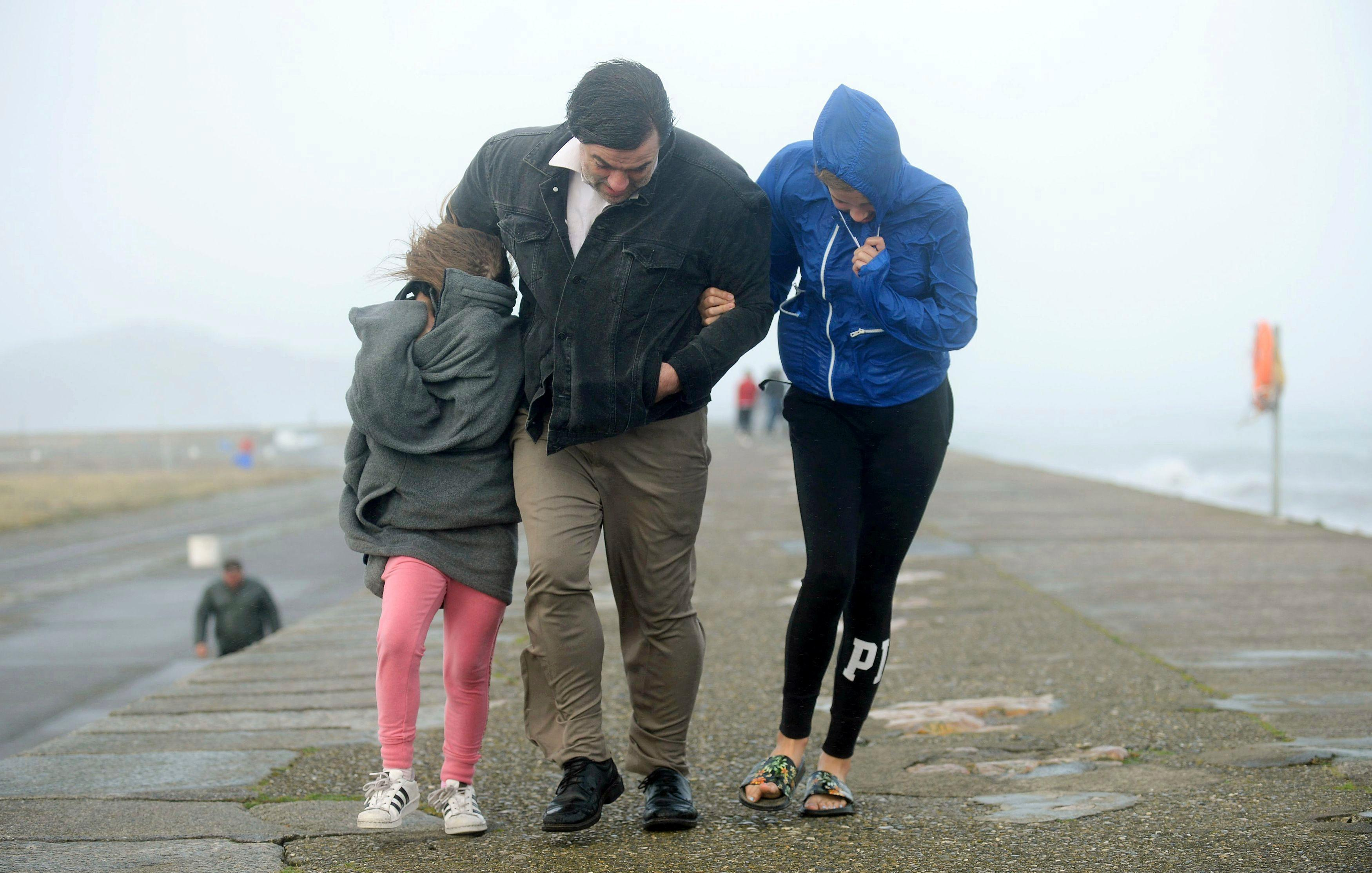 A family walks along a seawall during storm Ophelia on East Pier in Howth, Dublin, Ireland, as the remnants of Hurricane Ophelia batter Ireland and the United Kingdom with gusts of up to 80mph (129kph), Monday Oct. 16, 2017. Three people have been confirmed dead in Ireland in incidents related to Storm Ophelia. (Caroline Quinn/PA via AP)