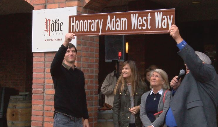 Adam West's son Perrin Anderson and Walla Walla Mayor Allen Pomraning hold up the Honorary Adam West Way sign as West's daughter Nina Tooley and wife Marcelle West look on.