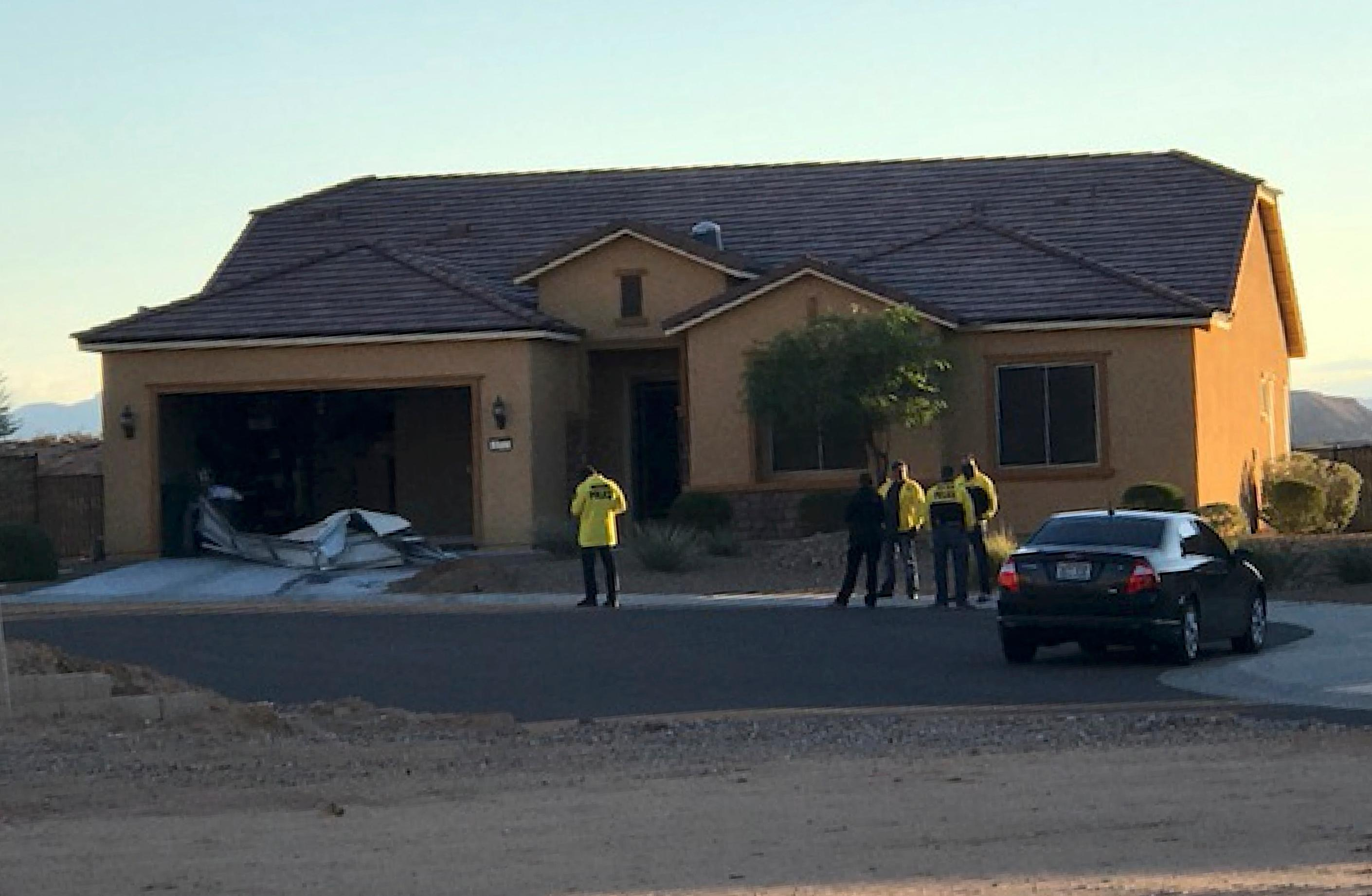 In this photo provided by the Mesquite, Nev., Police Department, police personnel stand outside the home of Stephen Paddock on Monday, Oct. 2, 2017, in Mesquite. Police identified Paddock as the gunman at a music festival Sunday evening. (Mesquite Police via AP)