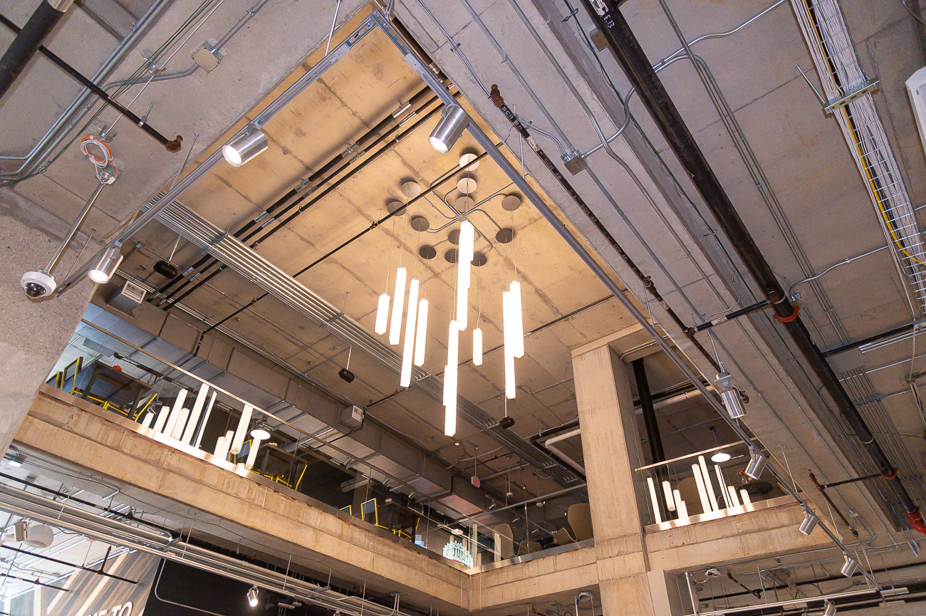 A modern, attractive chandelier hangs in the middle of the store where an opening joins the first and second floors. / Image: Phil Armstrong, Cincinnati Refined // Published: 9.24.19