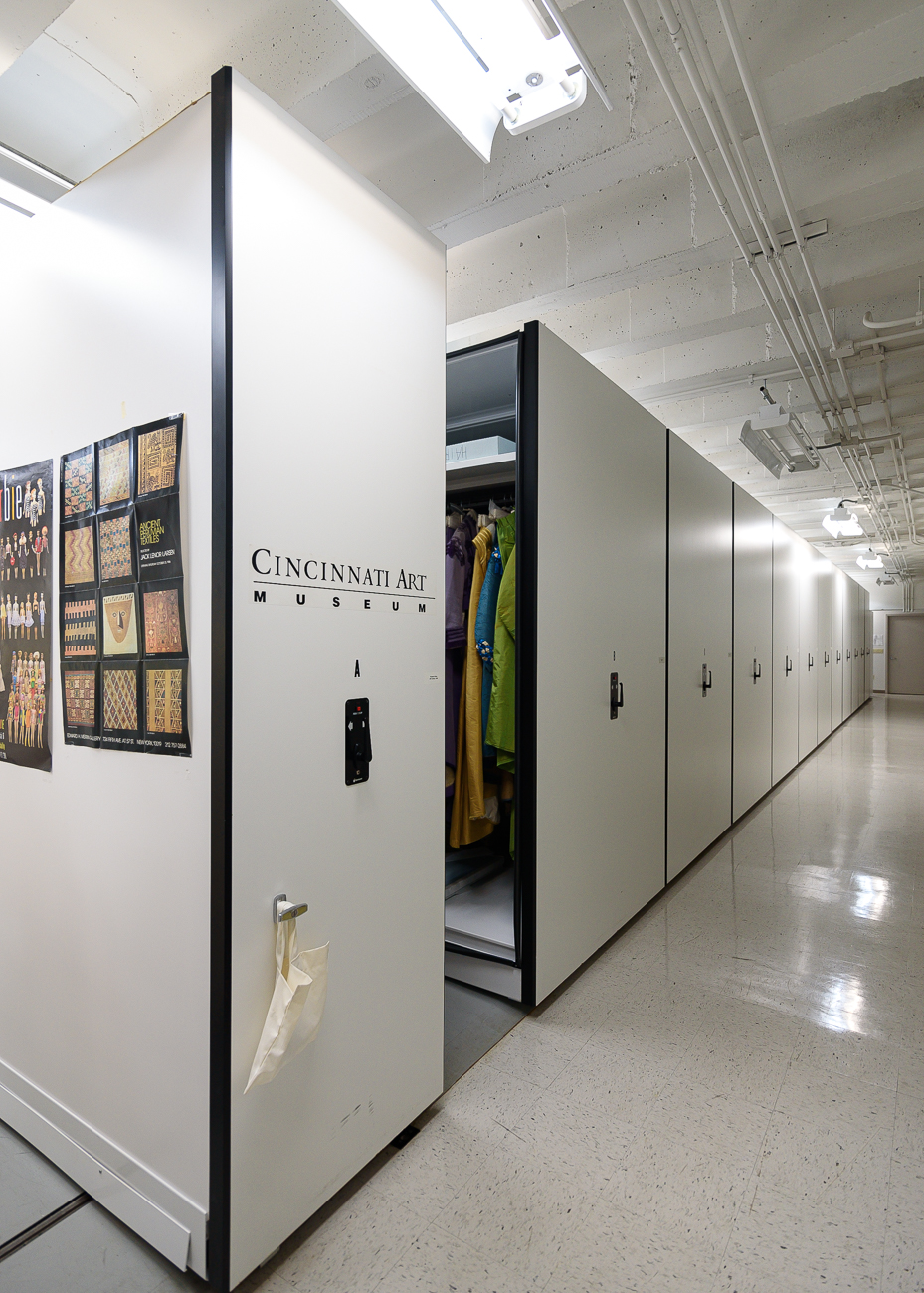 Deep within the lower levels of the Cincinnati Art Museum sits the Fashion Archive—an area where the museum's collection of around 15,000 garments and textiles ranging from the 5th century to today is safely stored. Temperature and humidity controlled and without windows, the facility is filled with movable shelves to pack as much storage into the space as necessary. The shelves move automatically when a control panel is pressed at the end of each row. It's not open to the public, though members of the Cincinnati Art Museum are occasionally invited down to see it on a guided tour. / Image: Phil Armstrong, Cincinnati Refined // Published: 2.18.20
