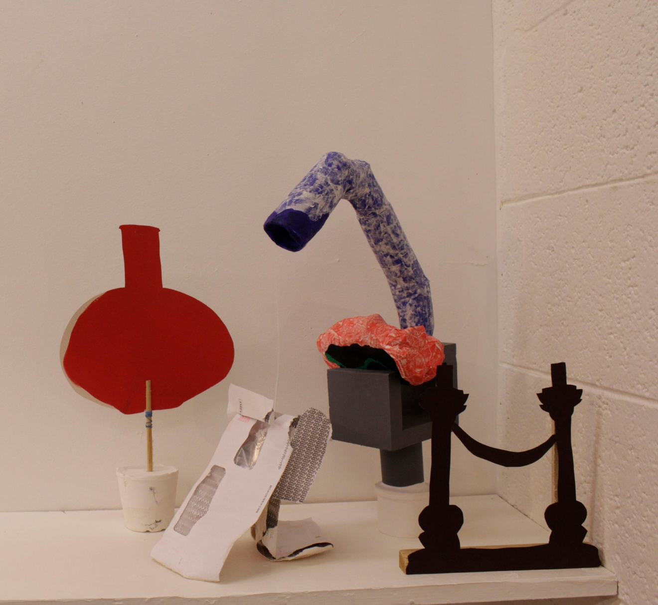 A selections of various relationships on a shelf  a) Red vase (a pinch and a weight) b) The real, real, real thing (two bill envelops)  c) Pieta (gray, blue, red and flocking)  d) Smile? Hang on? (black bookends) Mixed media 2014-2016  Photo courtesy Dawn Cerny