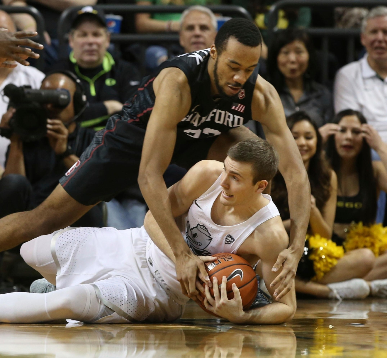 Stanford's Trevor Stanback, top, battles Oregon's Casey Benson for a loose ball during the first half of an NCAA college basketball game, Saturday, Jan. 21, 2017, in Eugene, Ore. (AP Photo/Chris Pietsch)