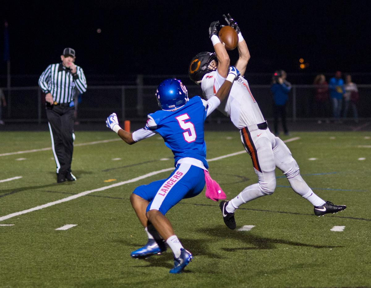 Crater Comets defensive back Dylan Kinney (#1) intercepts a pass intended for Churchill Lancers wide receiver Marshaun Tucker Jr. (#5). Churchill defeated Crater 63-21 on Friday at their homecoming game. Churchill remains undefeated with a conference record of 9-0. Photo by Dan Morrison, Oregon News Lab