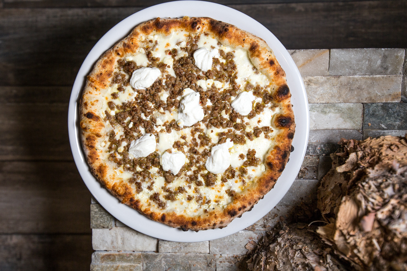 Bianca pizza: garlic oil base, fontina, goat cheese, fresh mozzarella, ricotta, parmigiano-reggiano, oregano, and extra virgin olive oil (This one has sausage added—Joe's pro tip!) / Image: Catherine Viox{ }// Published: 6.17.19