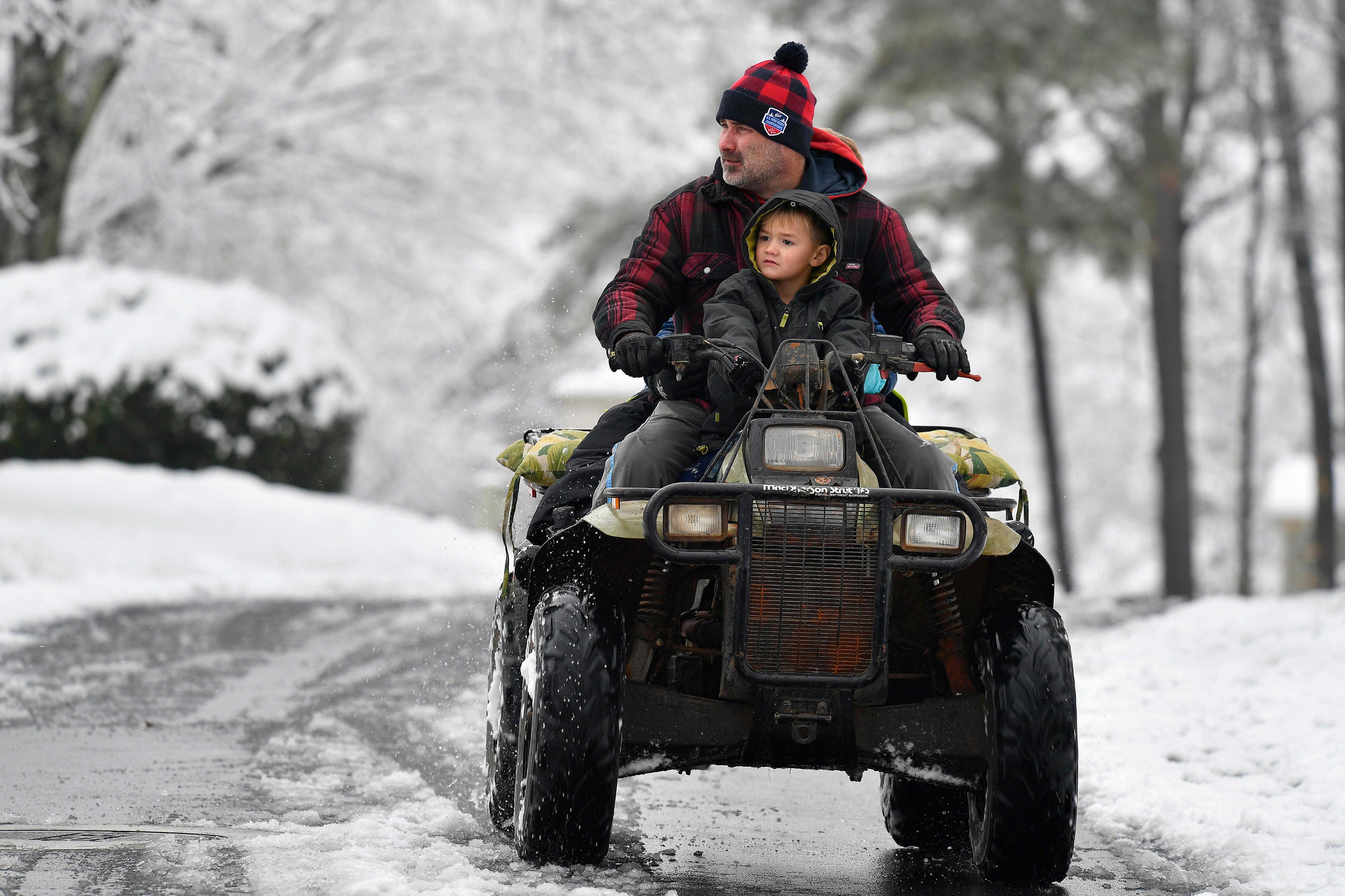 Jimmy Squibb and his son Nash ride an all-terrain vehicle as they survey their neighborhood after a heavy snow fall, Saturday, Dec. 9, 2017, in Kennesaw, Ga. The frigid temperatures behind a cold front combined with moisture off the Gulf of Mexico to bring unusual wintry weather to parts of the South. (AP Photo/Mike Stewart)