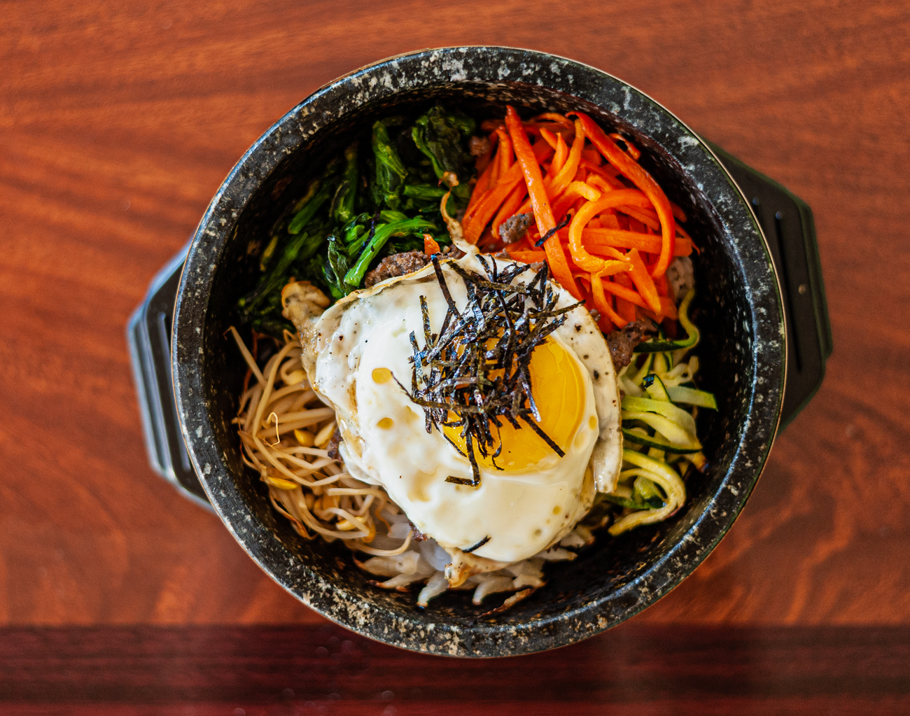 Dolsot Bibimbap: steamed rice topped with assorted stir fried vegetables and egg served in a sizzling hot stone bowl with spicy sauce on the side{&nbsp;}/ Image: Kellie Coleman // Published: 12.29.20<p></p>