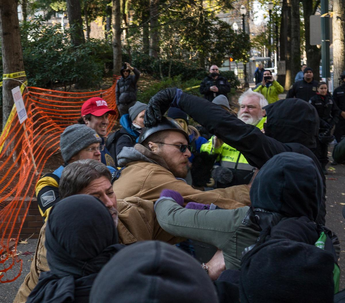 One of several brief fights erupts between members of Patriot Prayer and masked counter-protesters. A demonstration by the alt-right, conservative group Patriot Prayer began at 1 p.m. in Portland, Ore., on Saturday, December 9, to protest the homicide acquittal of Jose Ines Garcia Zarate, the undocumented immigrant who accidentally shot and killed Kate Steinle in San Francisco. The demonstration attracted a large crowd of counter-protesters and members of Antifa, and heated exchanges and several scuffles occurred between the two groups throughout the afternoon until the event's conclusion at 4 p.m., with at least one member of Patriot Prayer being detained by police and several demonstrators being injured. The rally began in Portland's Terry Schrunk Plaza and developed into a march along the Tom McCall Waterfront Park before ending at Terry Schrunk Plaza again. Photo by Kit MacAvoy, Oregon News Lab