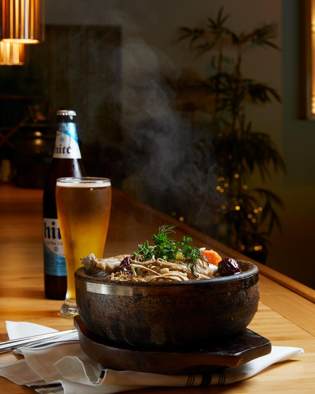 Samgyetang including whole cornish hen with simmered ginseng, garlic, and dates with a Hite Lager to drink / Image: Marlene Rounds // Published 9.18.18