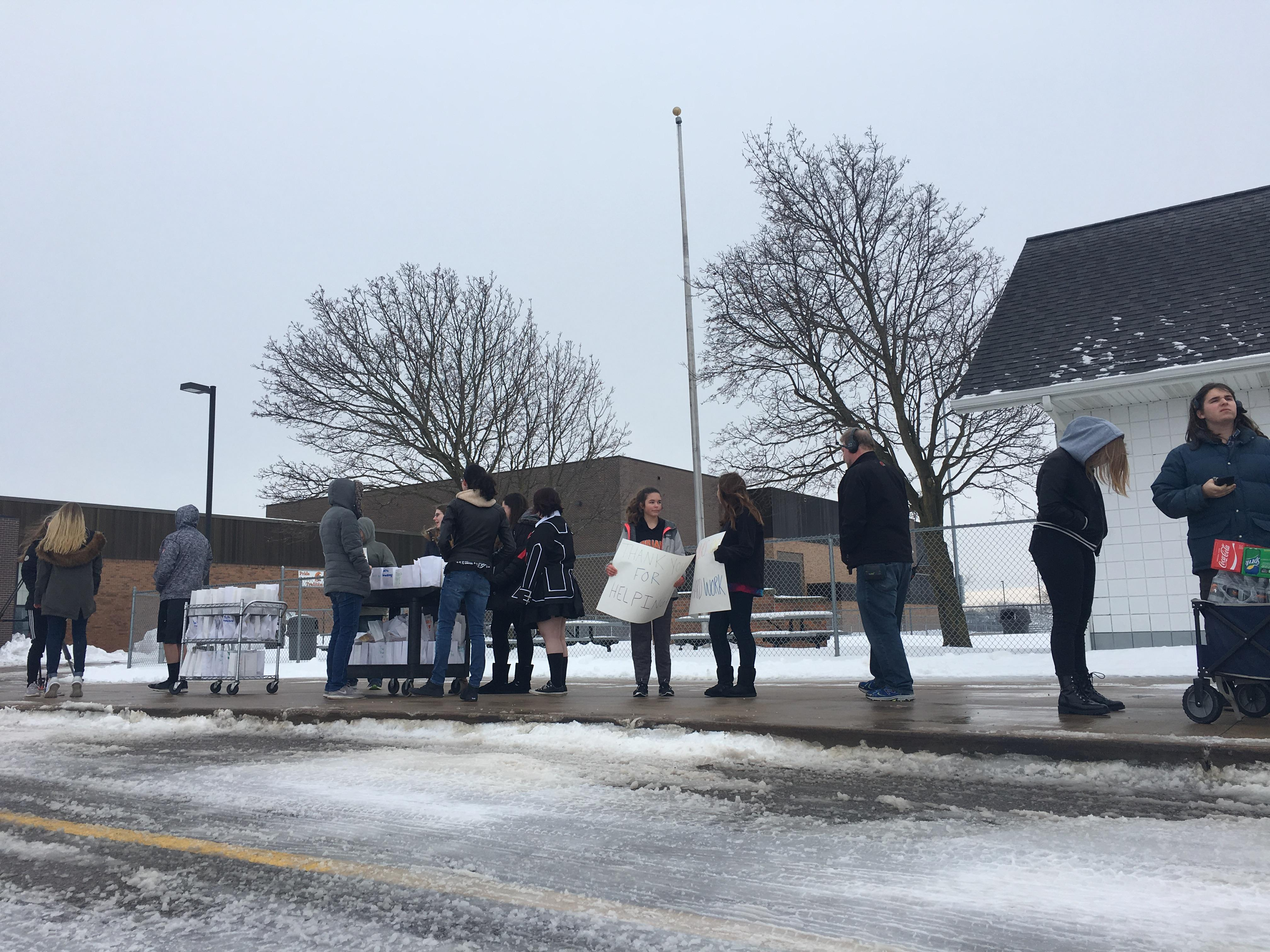Thornapple Kellogg High school students await with thank you signs as they give treats, beverages and words of encouragement to service workers and first responders. Feb. 14, 2019.{ } (WWMT/Jason Heeres)