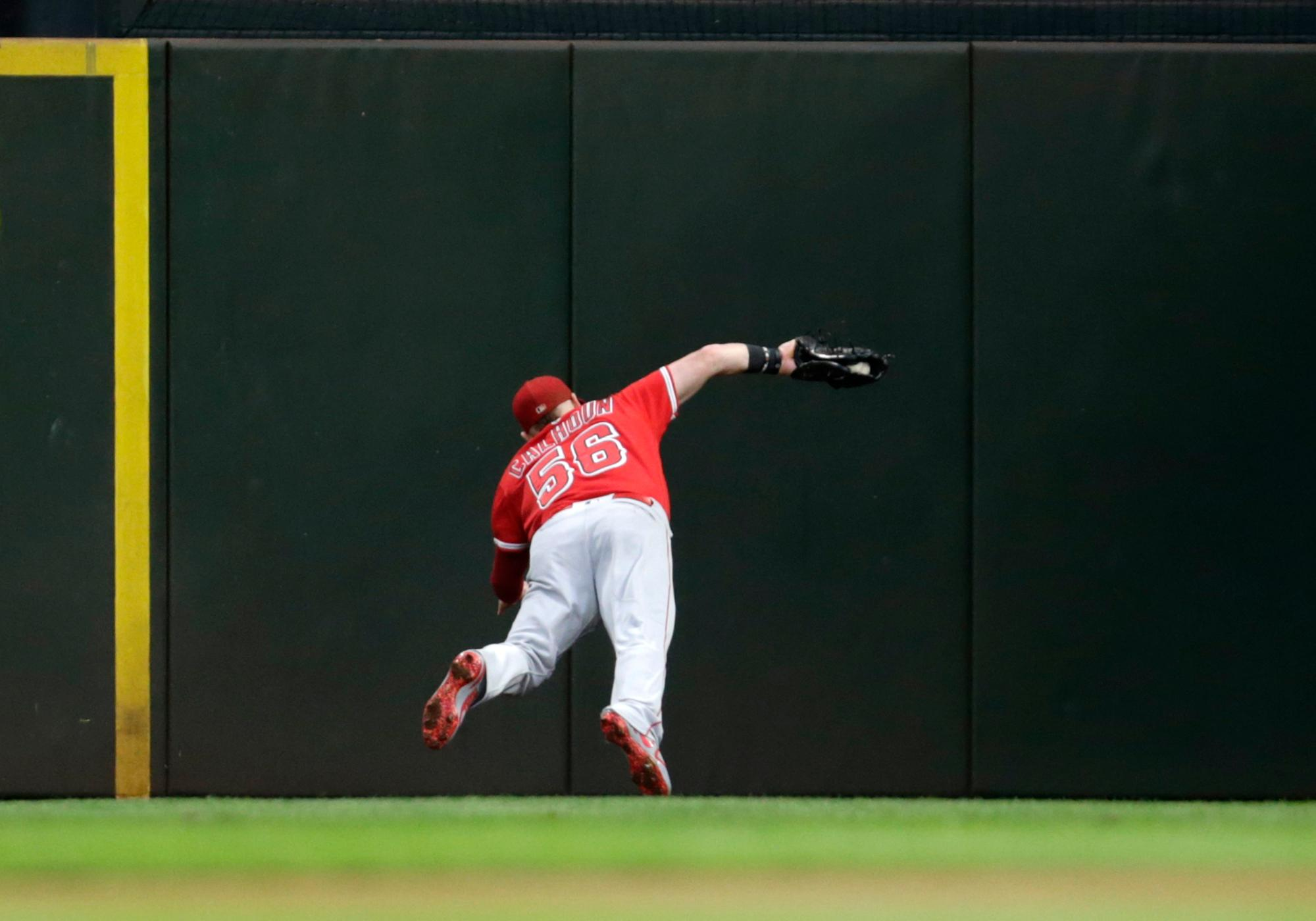 Los Angeles Angels right fielder Kole Calhoun dives for the ball but is unable to complete the catch, giving Seattle Mariners' Mitch Haniger a triple during the third inning of a baseball game Saturday, Sept. 9, 2017, in Seattle. Haniger scored in the inning. (AP Photo/John Froschauer)