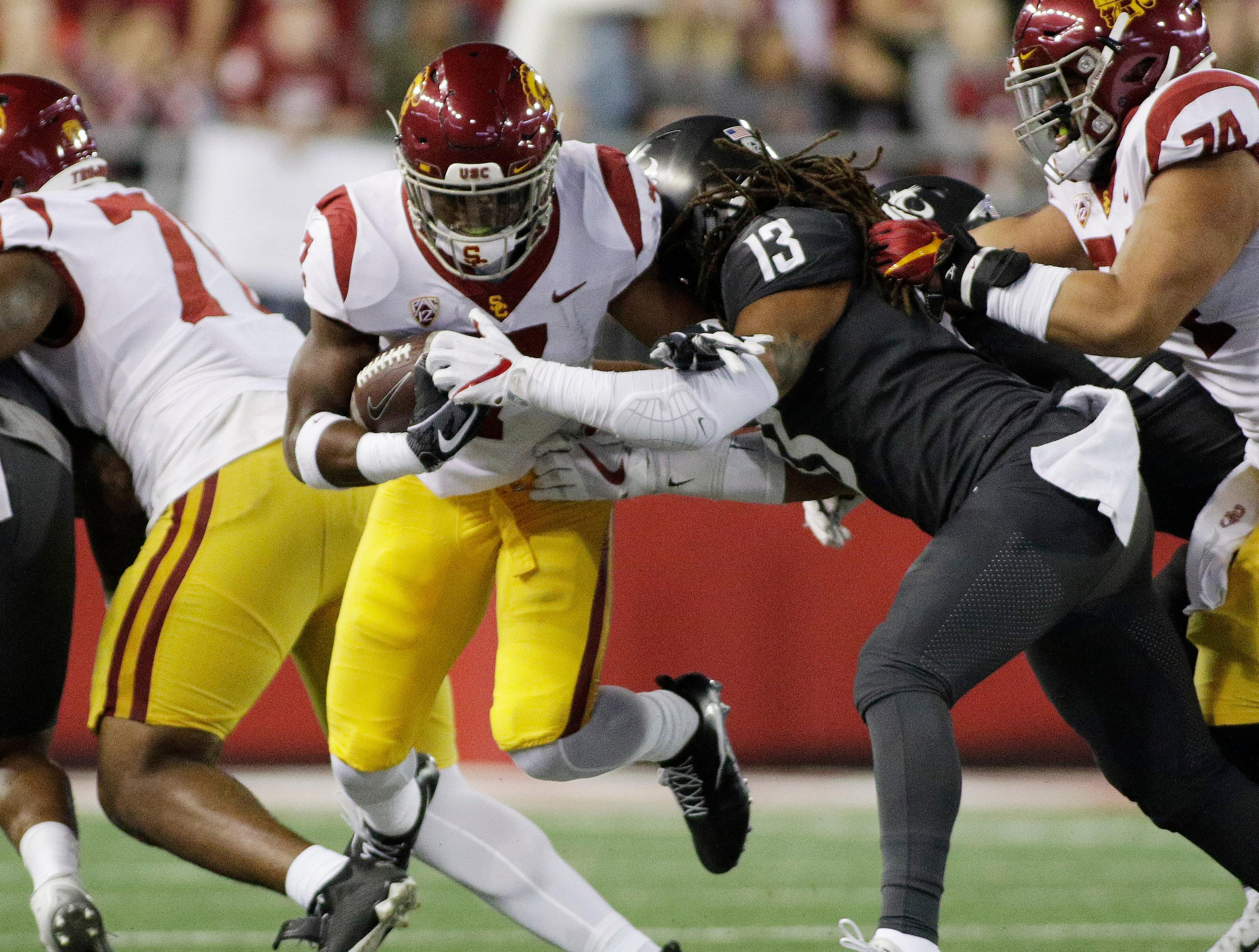 Washington State linebacker Jahad Woods (13) tackles Southern California tailback Stephen Carr (7) during the first half of an NCAA college football game in Pullman, Wash., Friday, Sept. 29, 2017. (AP Photo/Young Kwak)