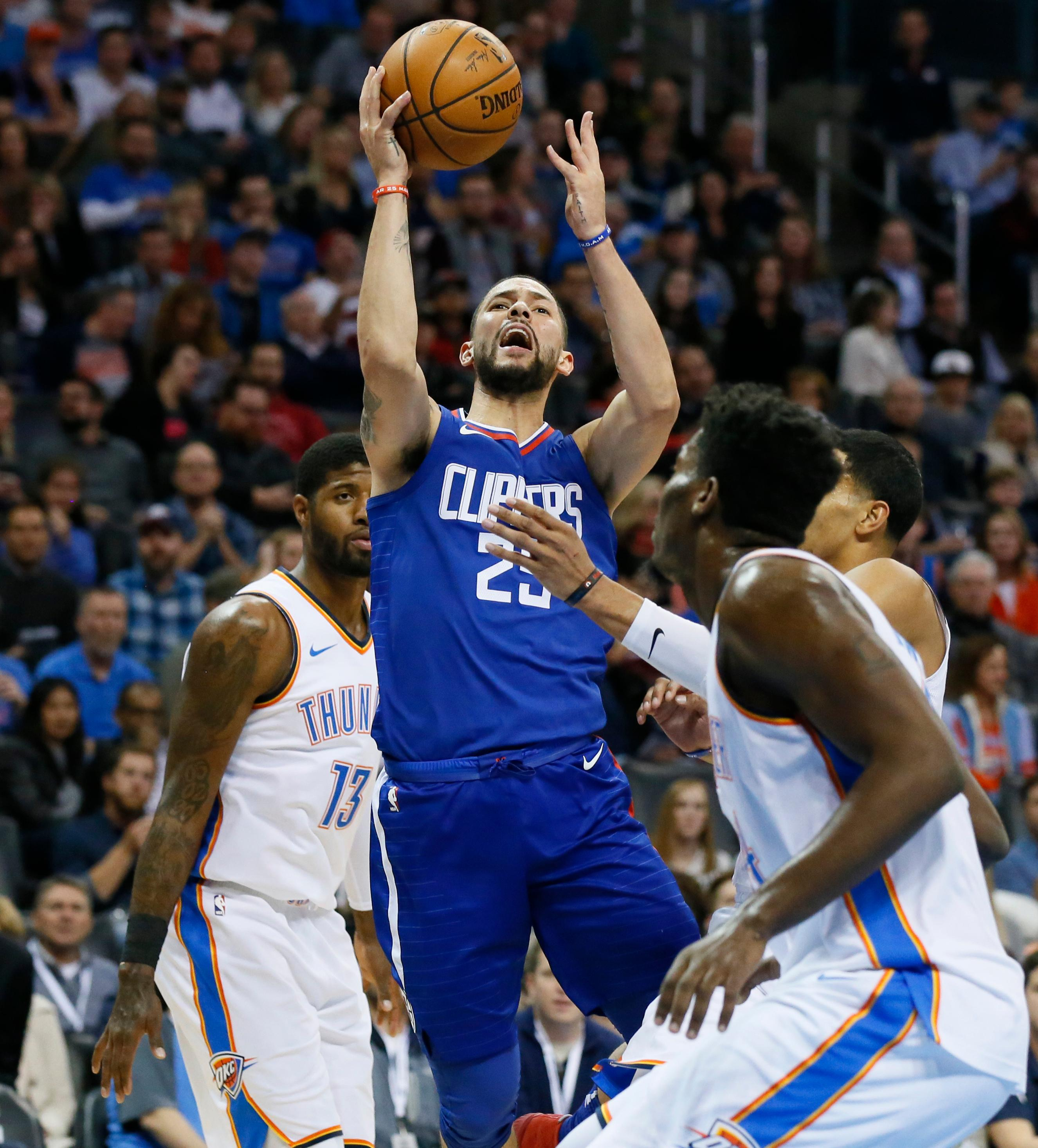 Los Angeles Clippers guard Austin Rivers (25) loses the ball as he drive between Oklahoma City Thunder forward Paul George (13), center Dakari Johnson, center and guard Andre Roberson, right, in the first half of an NBA basketball game in Oklahoma City, Friday, Nov. 10, 2017. (AP Photo/Sue Ogrocki)