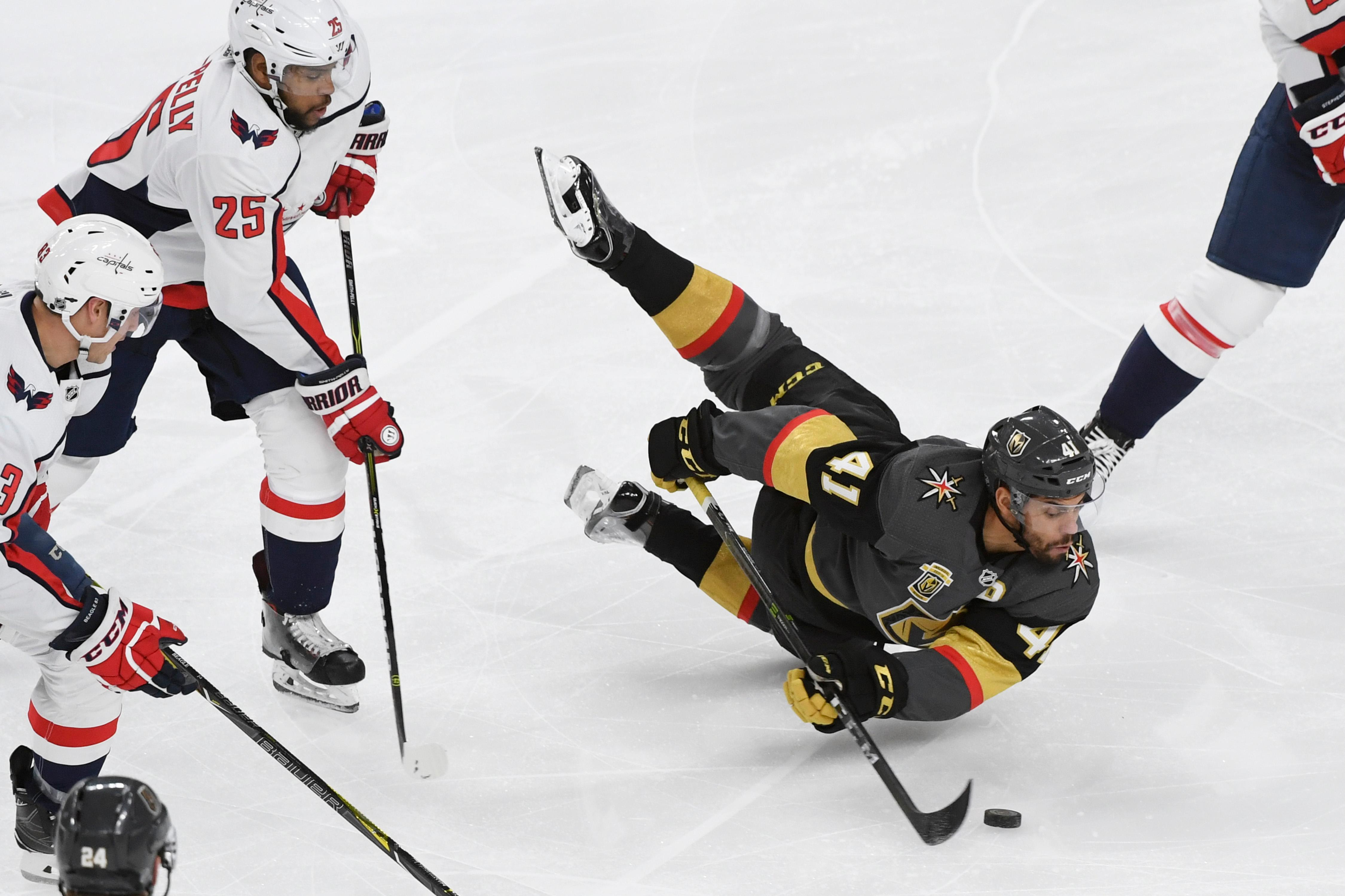 Vegas Golden Knights left wing Pierre-Edouard Bellemare (41) falls to the ice while trying to control the puck as Washington Capitals right wing Devante Smith-Pelly (25) comes up from behind during their NHL hockey game Saturday, December 23, 2017, at T-Mobile Arena in Las Vegas.  CREDIT: Sam Morris/Las Vegas News Bureau