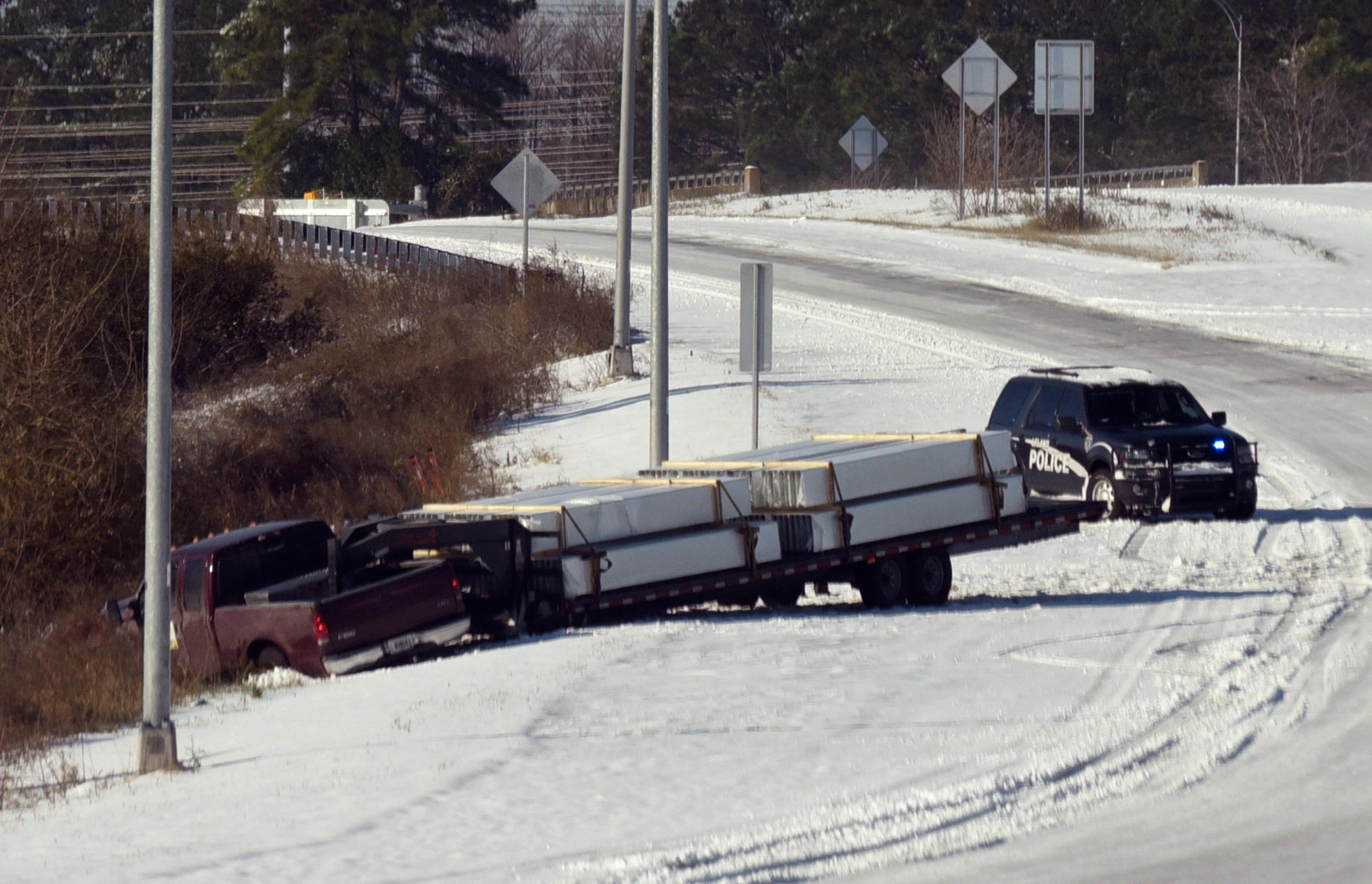 CORRECTS SOURCE TO THE STAR NEWS Leland Police look after a jack knifed truck along 74/76 in Leland, N.C. just before the Brunswick River Bridge Jan. 4, 2017. Just over 3 inches of snow covered the area after a winter storm moved through late last night. Areas along North Carolina's coast are reporting wind gusts of hurricane strength as part of a winter storm that's moving up the East Coast.   (Ken Blevins/The Star-News via AP)