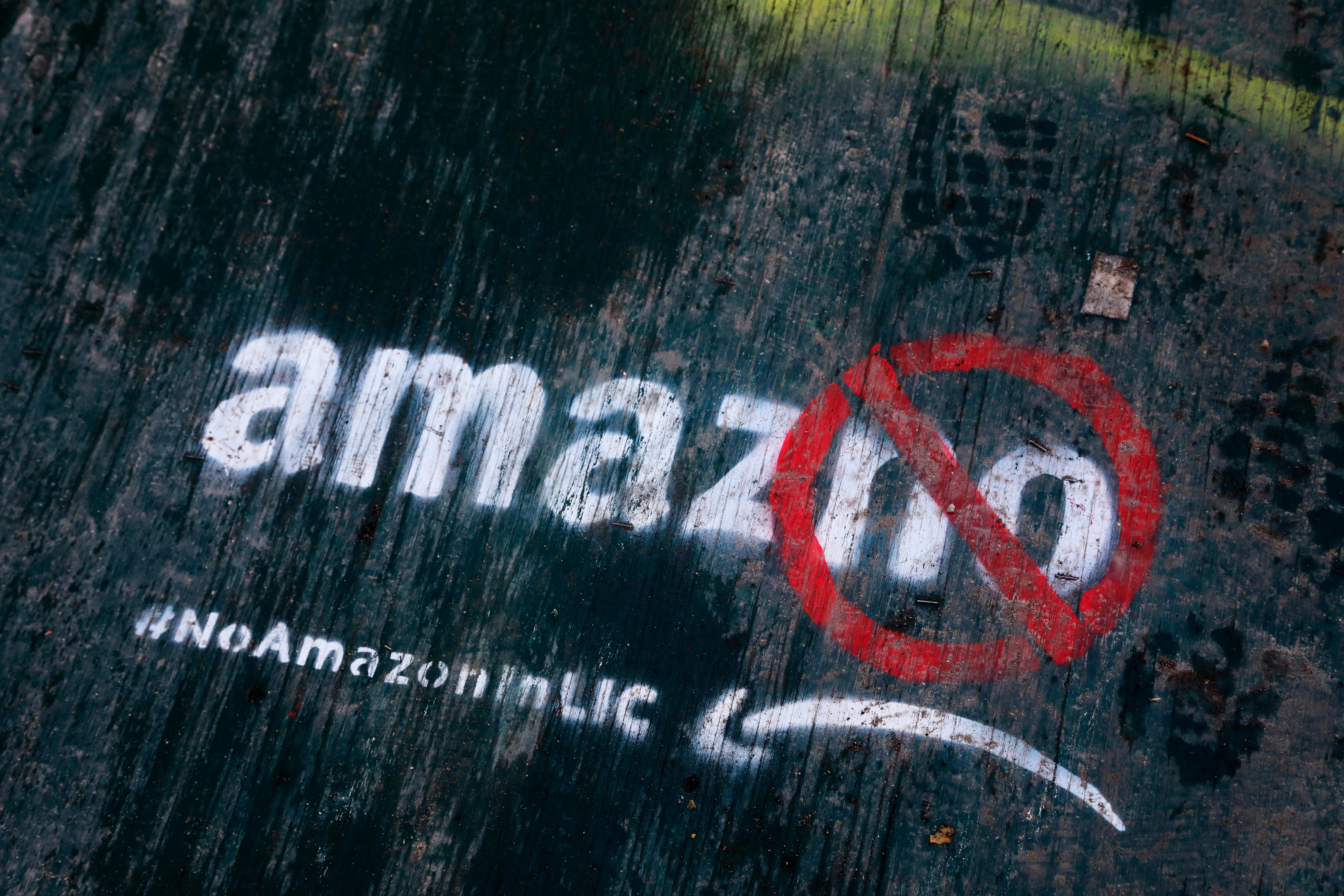 FILE- In this Nov. 16, 2018, file photo graffiti has been painted on a sidewalk by someone opposed to the location of an Amazon headquarters in the Long Island City neighborhood in the Queens borough of New York. Amazon said Thursday, Feb. 14, 2019, that it is dropping New York City as one of its new headquarter locations. (AP Photo/Mark Lennihan, File)