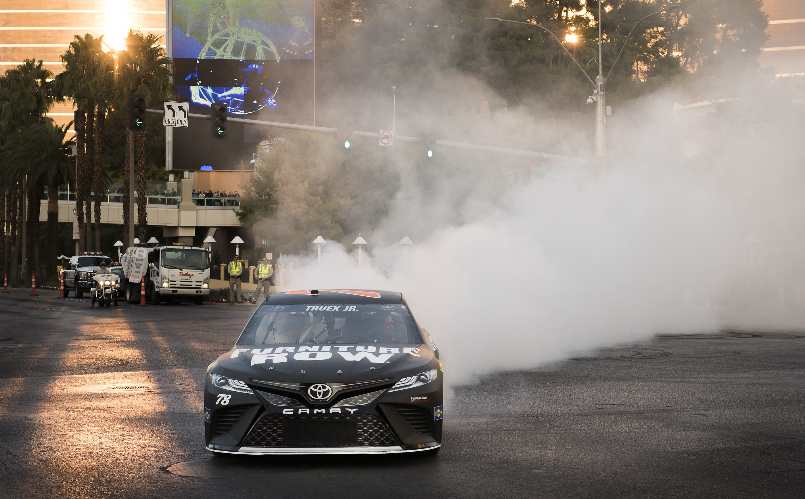 Driver Martin Truex, Jr., in his #78 Furniture Row Toyota Camry, leaves a trail a white smoke after burning out at the NASCAR Victory Lap on the Las Vegas Strip at the intersection of Las Vegas Blvd. and Spring  Mountain Road on Wednesday, Nov. 29, 2017. CREDIT: Mark Damon/Las Vegas News Bureau