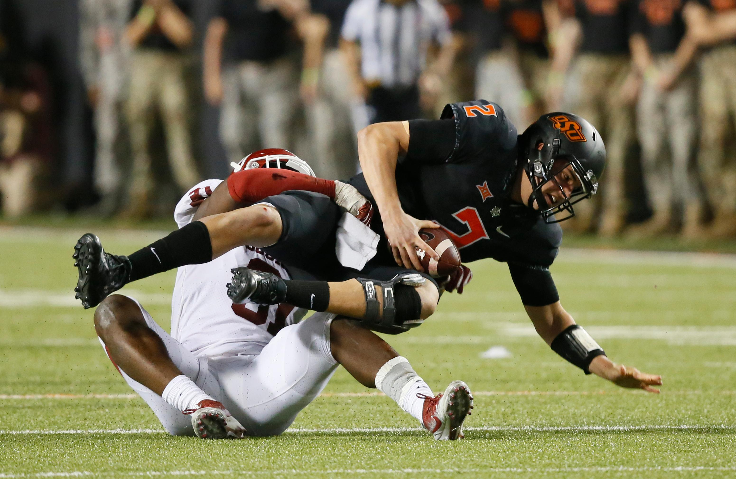 Oklahoma State quarterback Mason Rudolph (2) is sacked by Oklahoma defensive end Ogbonnia Okoronkwo, left, in the second half of an NCAA college football game in Stillwater, Okla., Saturday, Nov. 4, 2017. Oklahoma won 62-52. (AP Photo/Sue Ogrocki)
